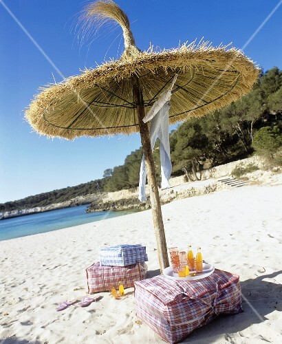 Bathing things and drinks under sunshade on sandy beach