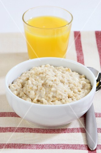 Porridge in a bowl and a glass of orange juice
