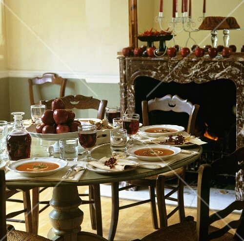 Tomato soup, apples and red wine on laid table (autumn)