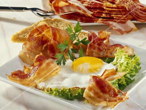 Fried egg and bacon with toast on lettuce leaf