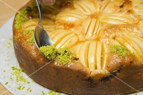 Sprinkling apple cake with chopped pistachios