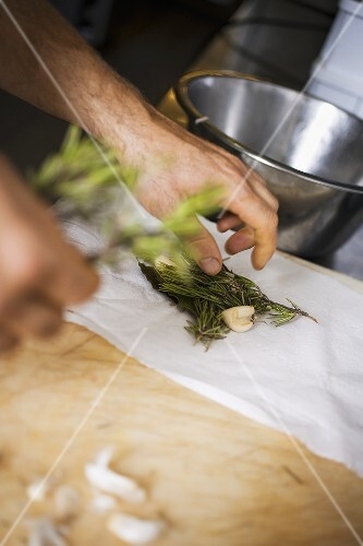Laying herbs and garlic on kitchen paper
