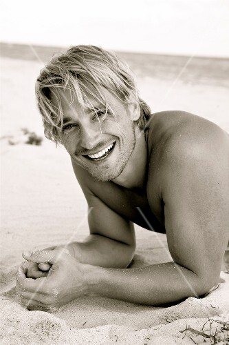Portrait of happy blonde man having fun while lying on beach, laughing, black and white