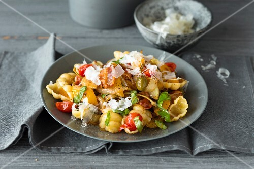 Pasta shells with tomatoes, olives, peppers and bacon