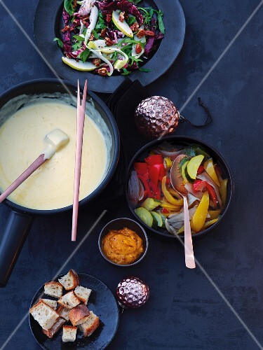 Bitter salads with pears and nuts, a cheese fondue and pickled vegetables