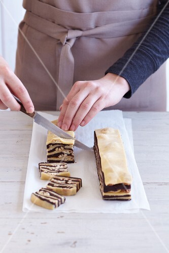 Zebra biscuits being made: layered pastry being sliced