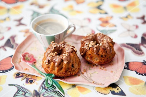 Mini nougat brittle Bundt cakes with apple served with a cup of coffee