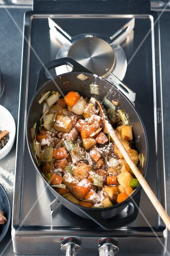 Venison ragout being made: vegetables being fried in a roasting tin