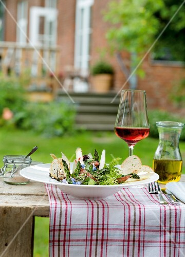 Asparagus salad with herbs and bread on a table outside