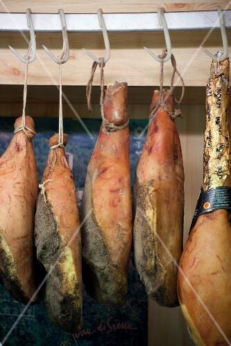 Whole Parma hams hanging on hooks