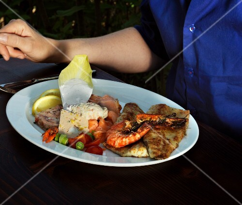 A person sitting at a table with a mixed fish platter