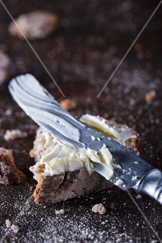 A piece of bread and butter with a knife