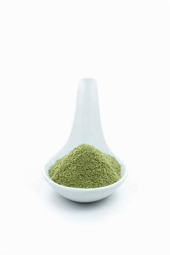Moringa powder on a spoon on a white surface