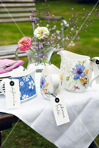 Various labelled milk jugs on a table outside
