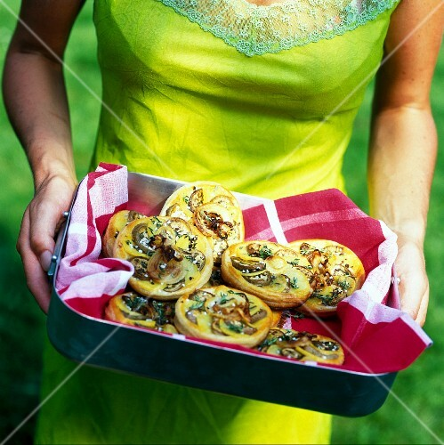 A woman carrying aubergine and potato tartlets in a baking tin