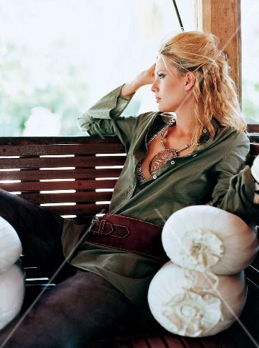 Contemplative blonde woman wearing necklace and tunic top relaxing on bench