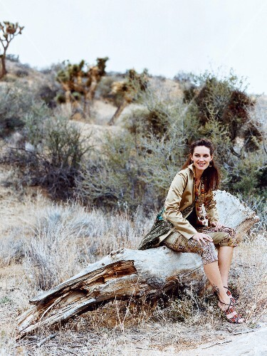 Pretty woman wearing folklore pattern satin jacket and capri pant sitting on gnarled log