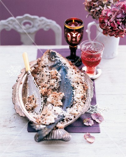 Bass with a salt crust on a table laid for Christmas dinner