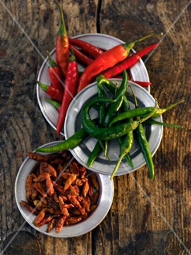 Plates of fresh and dried chilli peppers (seen from above)