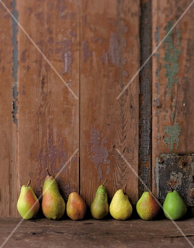 Various types of pears in a row against a wooden wall
