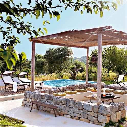 terrasse mit niedriger steinmauer pergola pool im garten italien bild kaufen. Black Bedroom Furniture Sets. Home Design Ideas