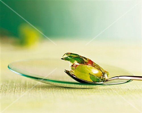 Grape and mint in jelly on spoon on a glass plate