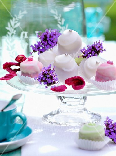 Mini cakes on a cake stand decorated with candied and fresh flowers