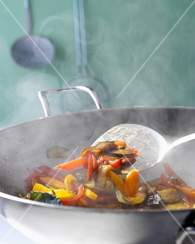 Steaming vegetables being fried in a wok