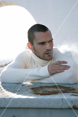 Man in white turtleneck sweater smoking a cigarette