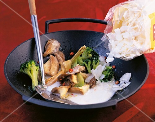 Coconut chips being added to broccoli, mushrooms and coconut milk in a wok