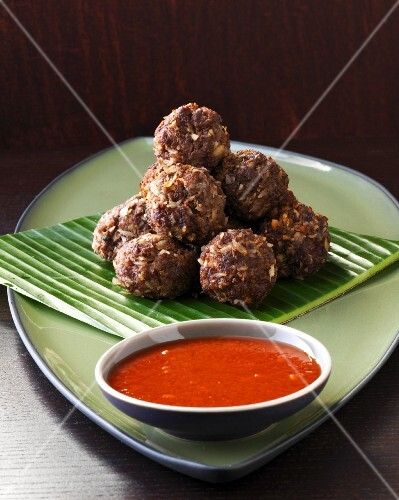Beef and coconut balls with a tomato dip on a banana leaf