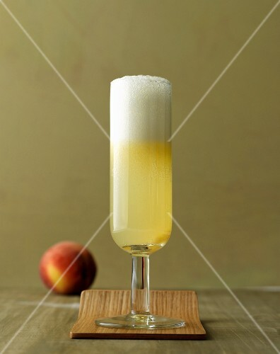 A classic bellini: cocktail with Prosecco and peaches in a champagne glass
