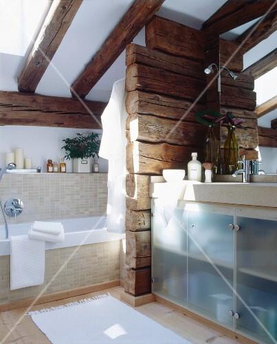 Badezimmer mit Dachschräge und Holzbalken als Raumteiler ...