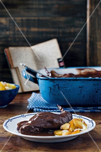 Rabbit stew with chocolate sauce and fried potatoes