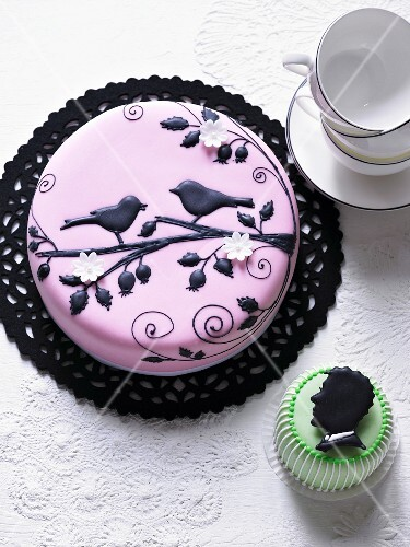 A cake decorated with pink fondant and black birds on a branch