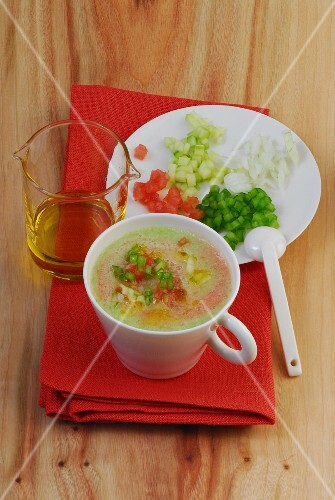 A cup of gazpacho with a plate of diced vegetables next to it