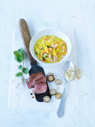 Saffron risotto with almonds and mint served with lamb fillet