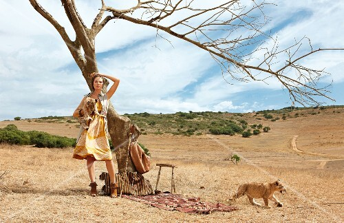 Woman holding lion cub and standing in front of bare tree