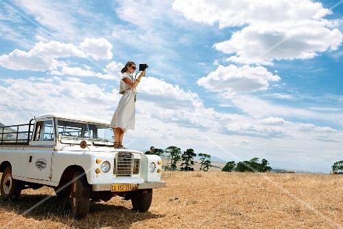 Woman standing on jeep and filming African plains