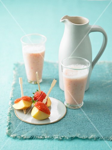 A fruit shake with strawberry and peach skewers