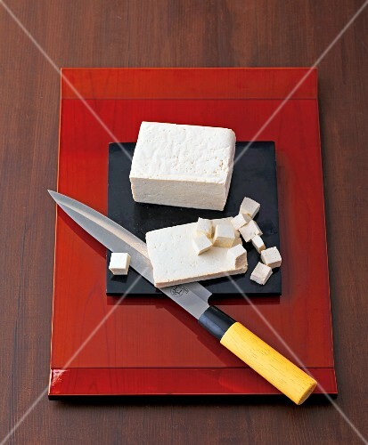A block of tofu, sliced and diced, with a knife on a chopping board