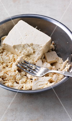 Tofu being mashed with a fork