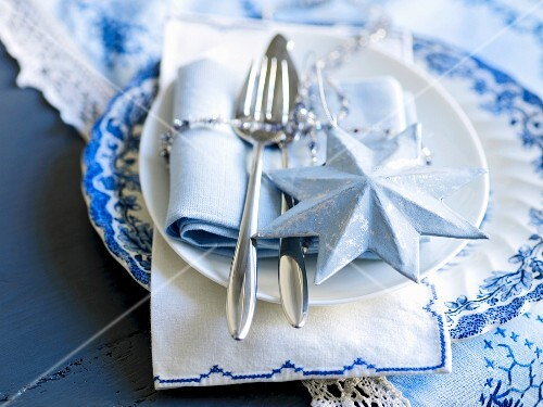 A place setting decorated for Christmas in blue and white