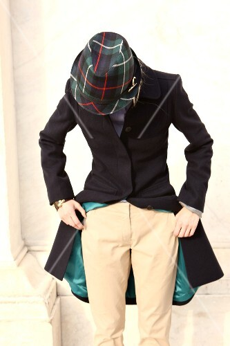 Woman wearing loden coat, pants and plaid hat standing, looking down