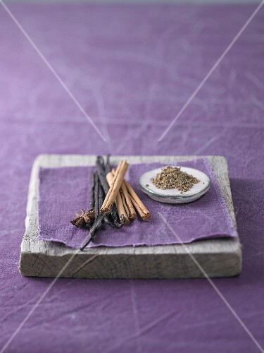 An arrangement of anise seeds, star anise, cinnamon sticks and the pods