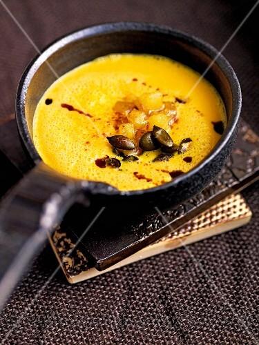Cream of pumpkin soup with cinnamon apples and pumpkin seeds