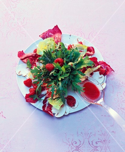 A mixed leaf salad with fresh raspberries and raspberry oil