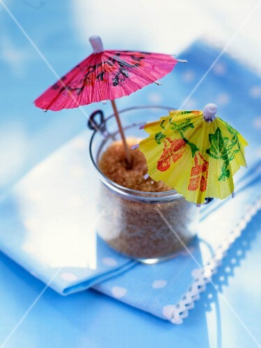 A glass of cane sugar decorated with two colourful cocktail umbrellas