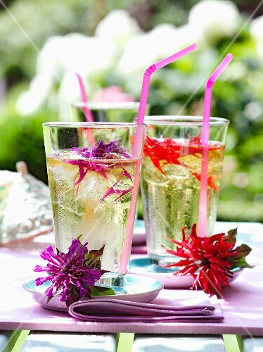 Glasses with straws and flowers on a garden table