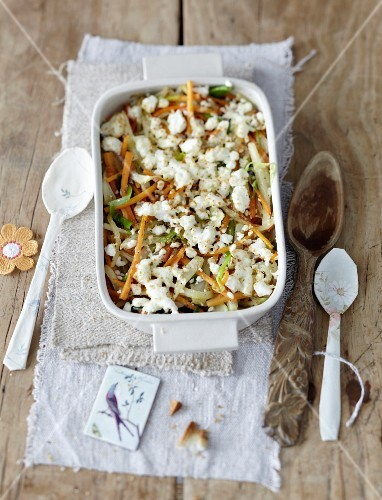 Gratinated spring vegetables with sheep's cheese in a baking dish